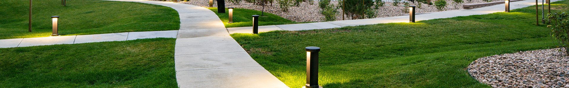 Lite Pathway with grass to apt buildings Units Available in Colorado Springs, CO | Copper Range Apartment Homes