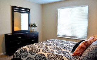 Bedroom with plenty of natural light, queen size bed, dresser and mirror