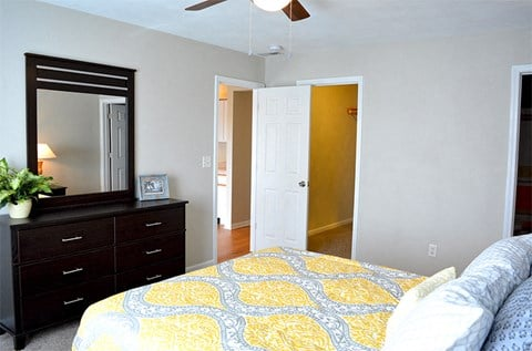 Bedroom with queen size bed, dresser, mirror, and walk-in closet