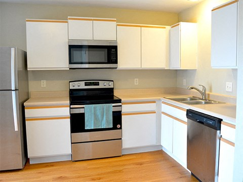 Updated kitchen with stainless steel appliances and hardwood flooring