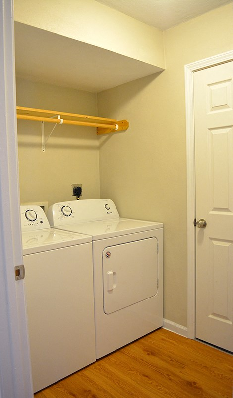 In-unit laundry room with full-size washer and dryer and hanging rack