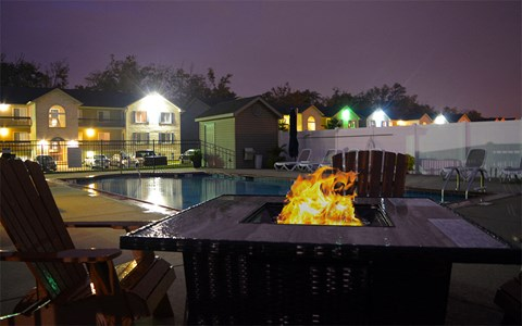 Night time image of fire pit located next to the pool
