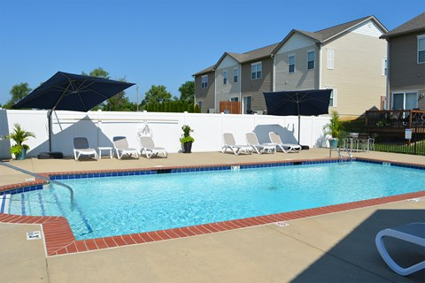 Outdoor pool with lounge chair seating and umbrellas