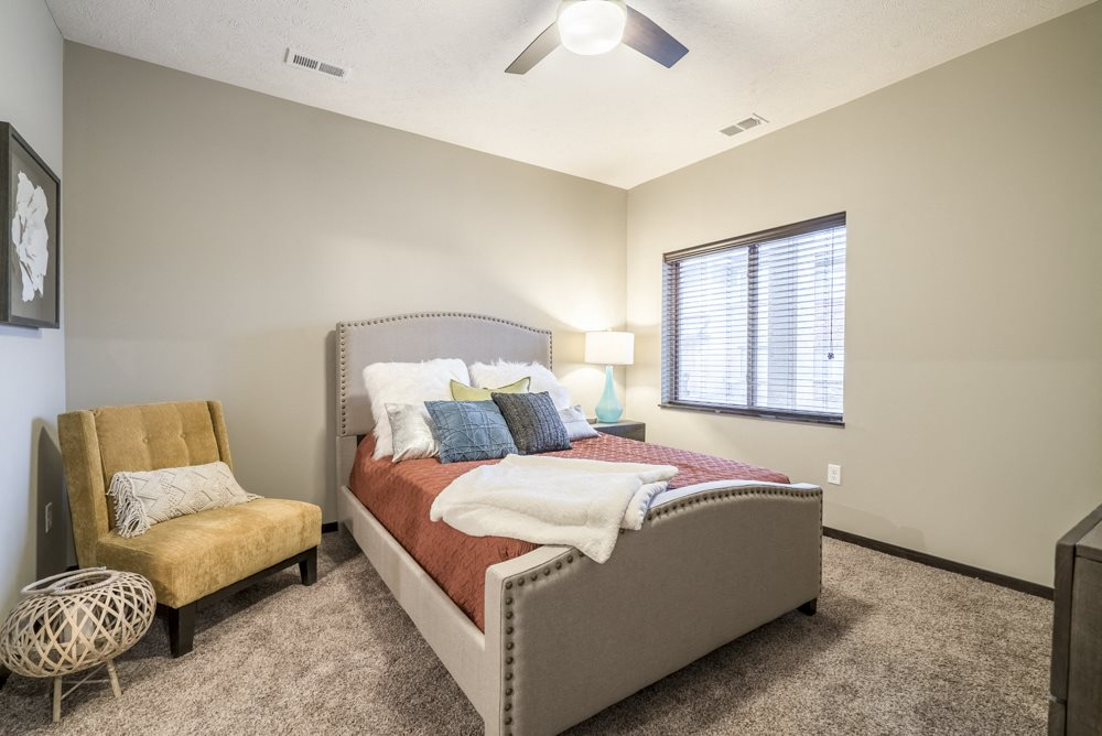Interiors-1 bedroom apartment bedroom with ceiling fan, queen bed and chair