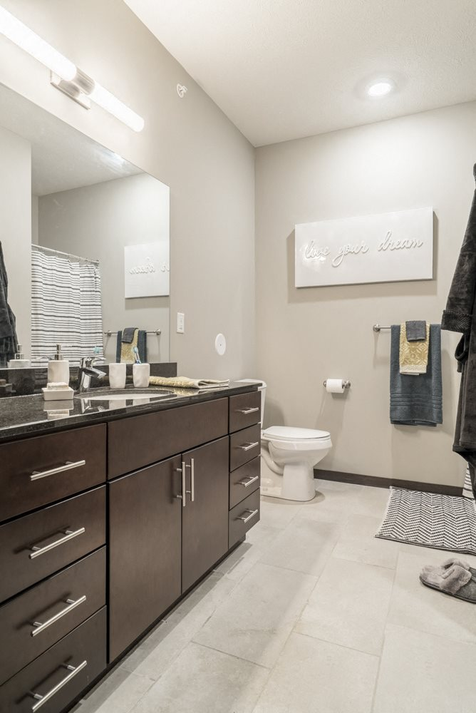 Interiors-Bathroom in traditional design scheme with dark cabinetry, light tile floors and granite countertops