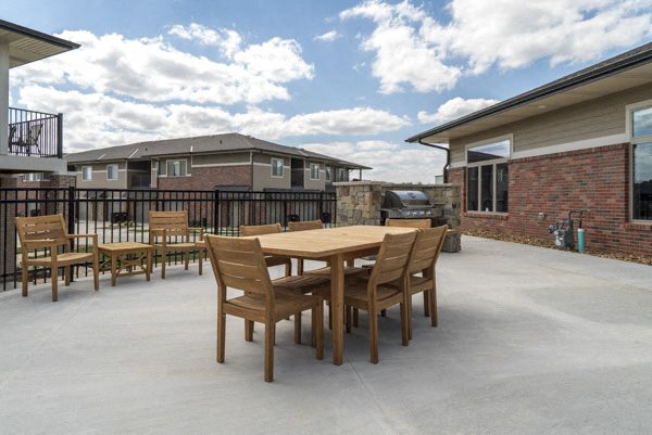 Outdoor tables and grills near the pool at The Villas at Falling Waters townhomes in west Omaha