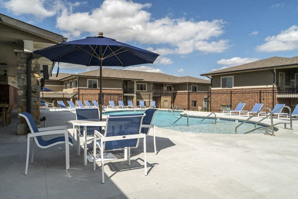 Resort-style pool with chairs and umbrellas at The Villas at Falling Waters in west Omaha