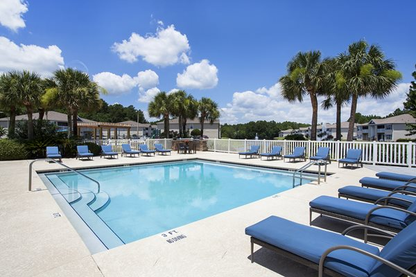 A beautiful Florida sky reflects off the sleek swimming pool water at Crystal Lake Apartments in Pensacola, FL