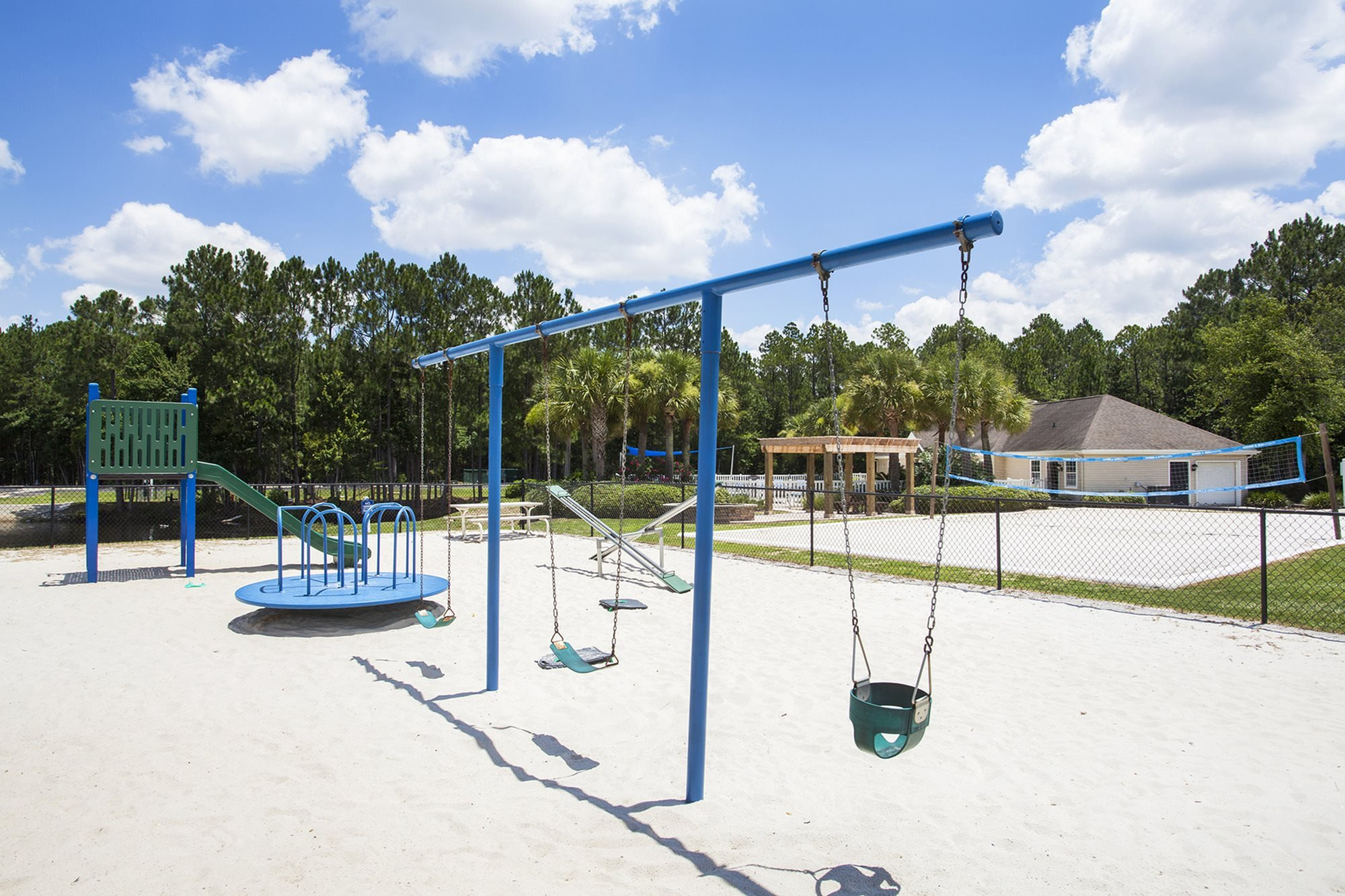 Tropical white sand sits under the playground area and volleyball court at Crystal Lake Apartments in Pensacola, FL