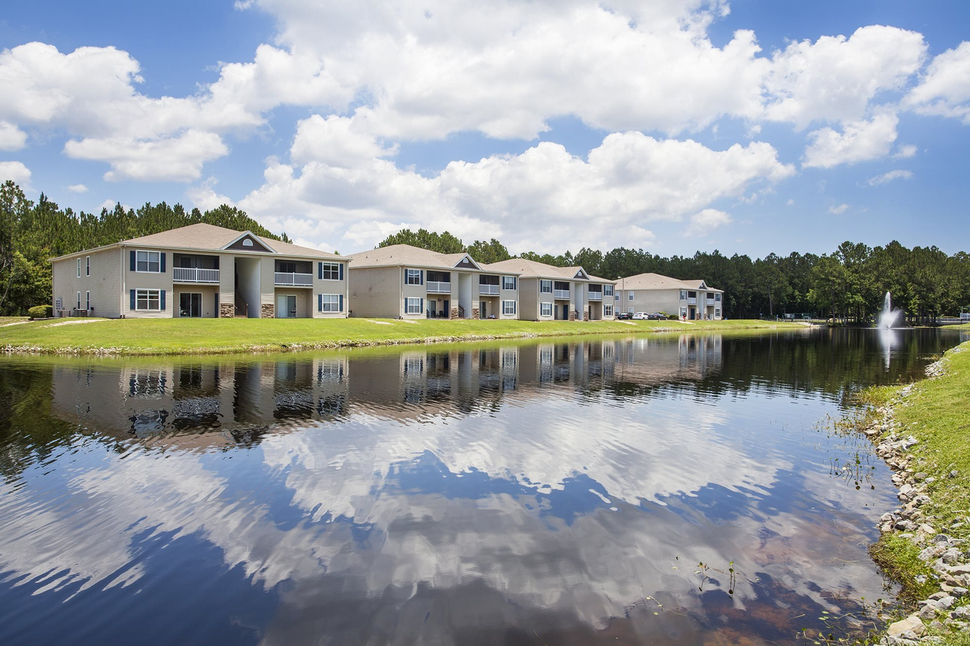 Ripples in the water of the stocked lake reflect the Florida sky like a painting at Crystal Lake Apartments in Pensacola, FL