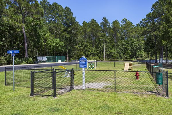 A teeter-totter, jumping hoop, wooden ramp and more in the dog park at Crystal Lake Apartments in Pensacola, FL