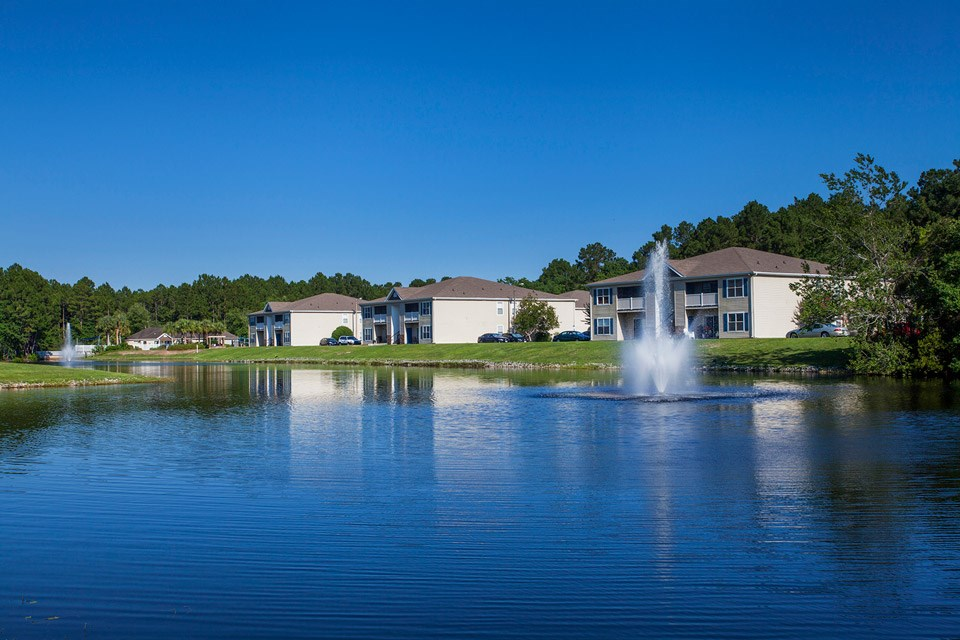 The majestic fountains shoot high in the air over the blue stocked lake at Crystal Lake Apartments in Pensacola, FL