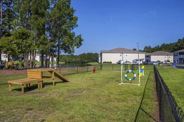 Near the apartments sits the spacious dog park with canine-friendly objects at Crystal Lake Apartments in Pensacola, FL
