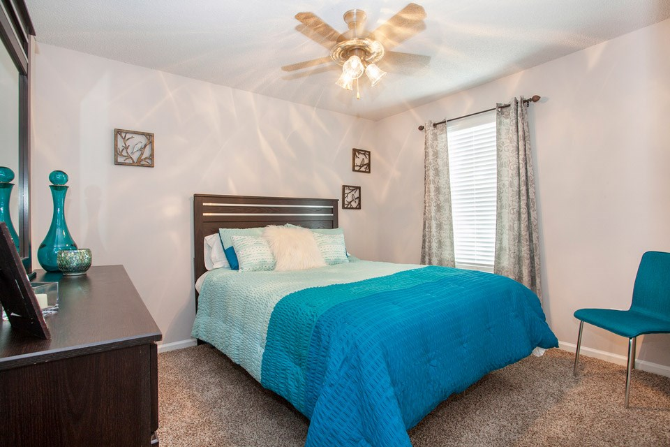 A ceiling fan sits over a tan and aquamarine furnished bedroom at Crystal Lake Apartments in Pensacola, FL