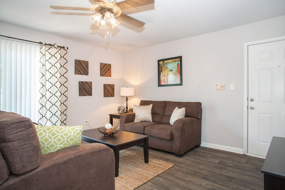 A comfortably furnished living room sits just inside the front door of a unit at Crystal Lake Apartments in Pensacola, FL