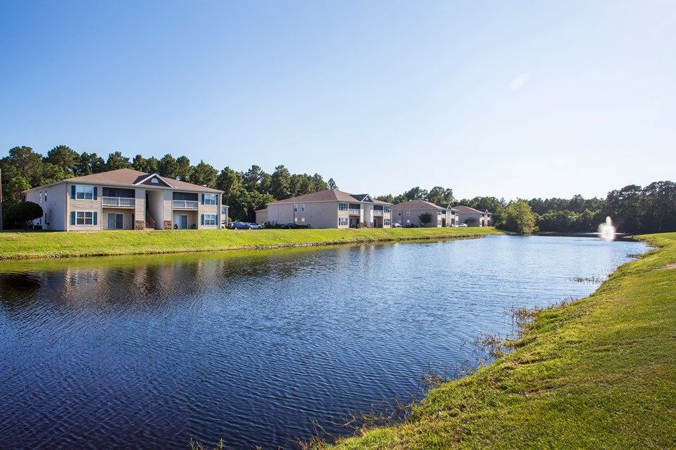 Multiple units sit overlooking the beautiful blue stocked lake at Crystal Lake Apartments in Pensacola, FL