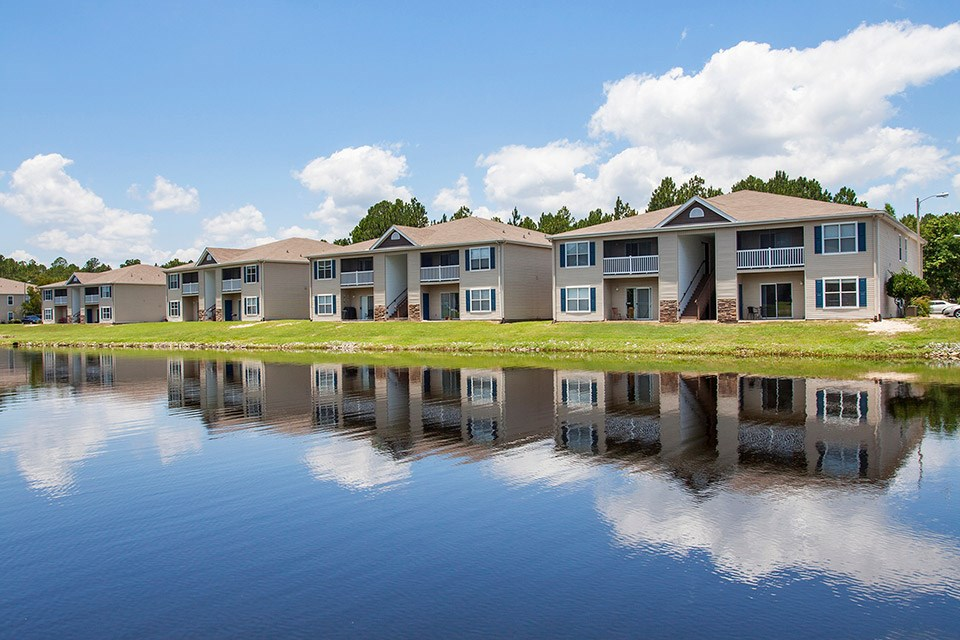 Lakeside apartment units and big blue sky reflect off the stocked lake at Crystal Lake Apartments in Pensacola, FL