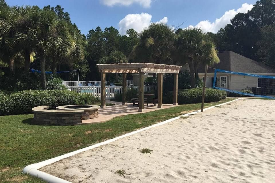 The outdoor fire pit sits next to the white sand volleyball court at Crystal Lake Apartments in Pensacola, FL