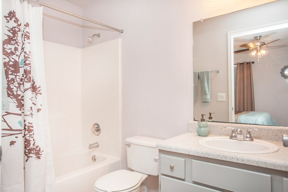 A spotless bathroom with complimentary sea green and burnt red furnishings at Crystal Lake Apartments in Pensacola, FL