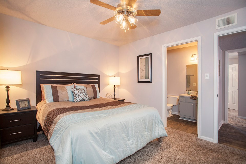 A mix of modern wood floors and carpet makes the bedroom and bathroom at Crystal Lake Apartments in Pensacola, FL