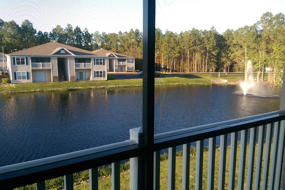 A balcony view overlooks the stocked lake and fountain at Crystal Lake Apartments in Pensacola, FL