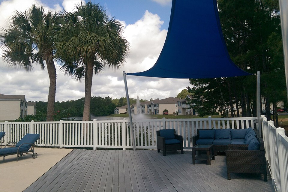 A large blue overhang protects community patio furniture poolside at Crystal Lake Apartments in Pensacola, FL