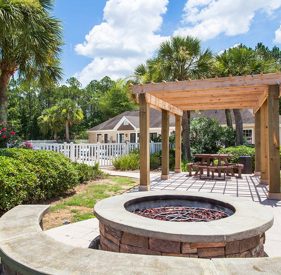 Near the swimming pool, the large fire pit sits ready for a cool evening at Crystal Lake Apartments in Pensacola, FL
