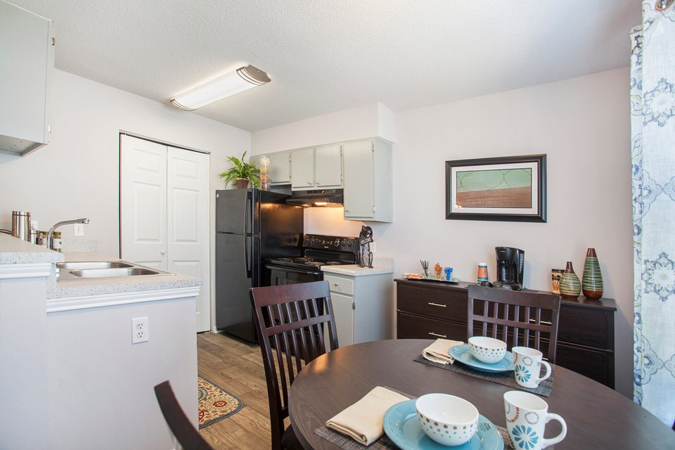 A spacious kitchen with sleek black appliances sits next to a dining table at Crystal Lake Apartments in Pensacola, FL