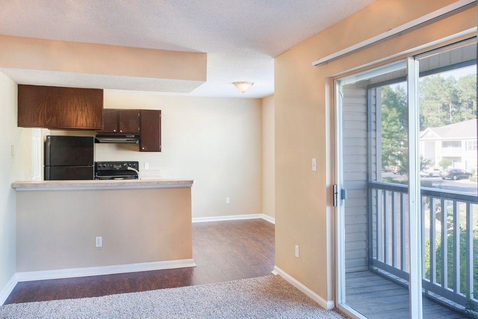 To the left, a black and wood finished kitchen; the right, the balcony overlooking Crystal Lake Apartments in Pensacola, FL