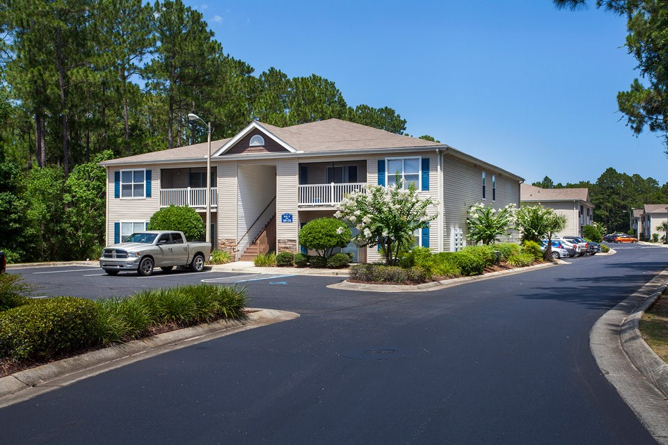 The road connecting units and parking lots lined by beautiful landscaping at Crystal Lake Apartments in Pensacola, FL