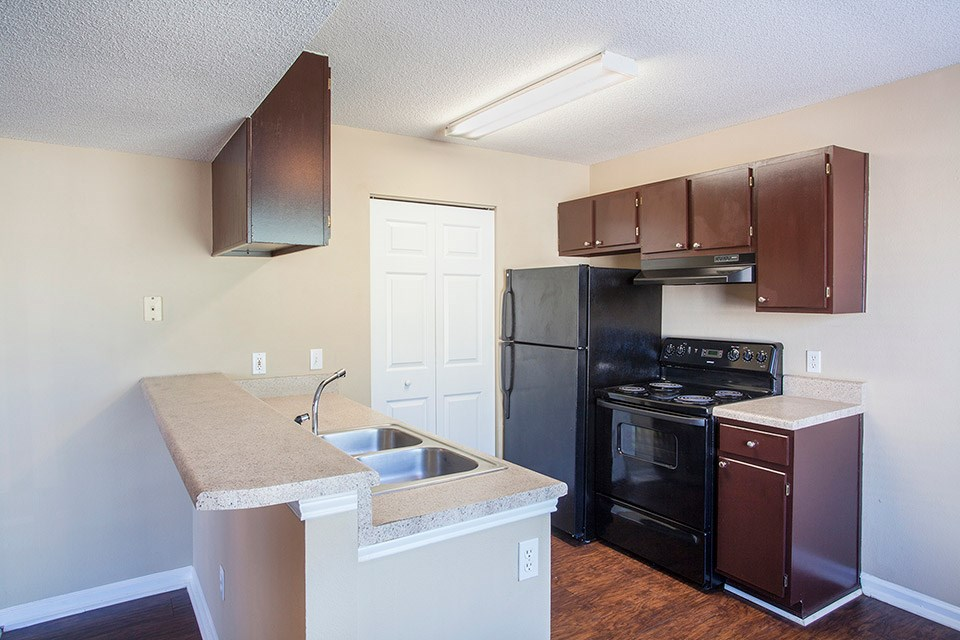 A black refrigerator and range sit under glossy brown kitchen cabinets at Crystal Lake Apartments in Pensacola, FL