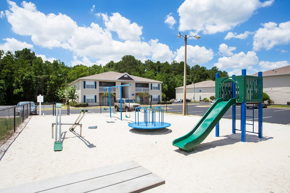 The large white sand playground area with slide, swings and more at Crystal Lake Apartments in Pensacola, FL