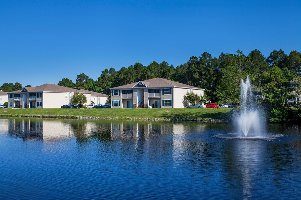 A beautiful fountain creates ripples in the water near lakeside apartments at Crystal Lake Apartments in Pensacola, FL