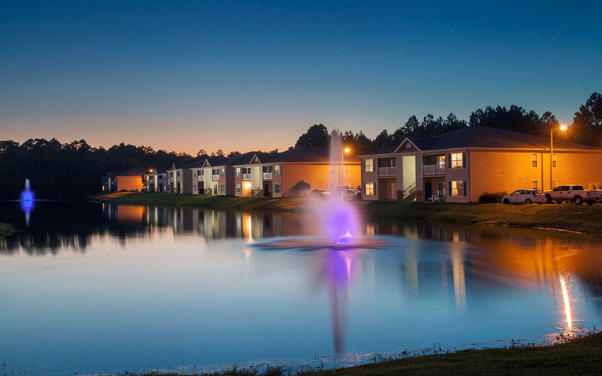 Two beautiful neon-lit fountains sit in the stocked lake at Crystal Lake Apartments in & Crystal Lake | Apartments in Pensacola FL azcodes.com