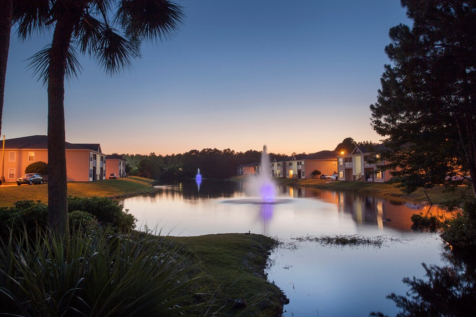 Two beautiful neon-lit fountains shower the stocked lake at Crystal Lake Apartments in Pensacola, FL