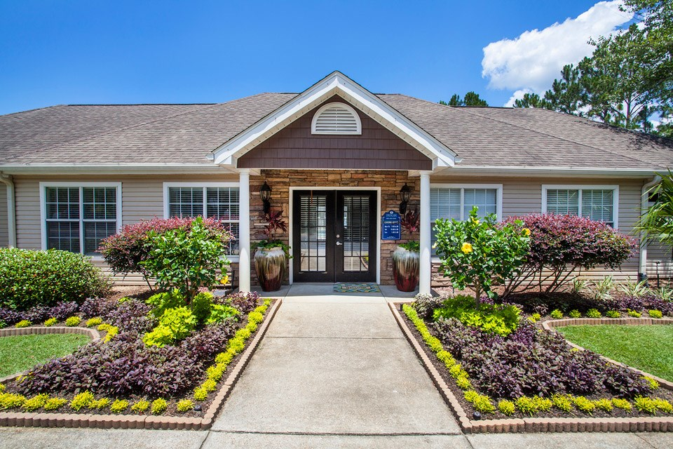 Beautifully landscaped plants sit in front of the entrance to the leasing office at Crystal Lake Apartments in Pensacola, FL
