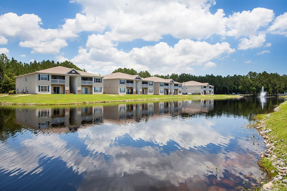 Across the seemingly painted lake surface sits four apartment buildings of the Crystal Lake Apartments in Pensacola, FL