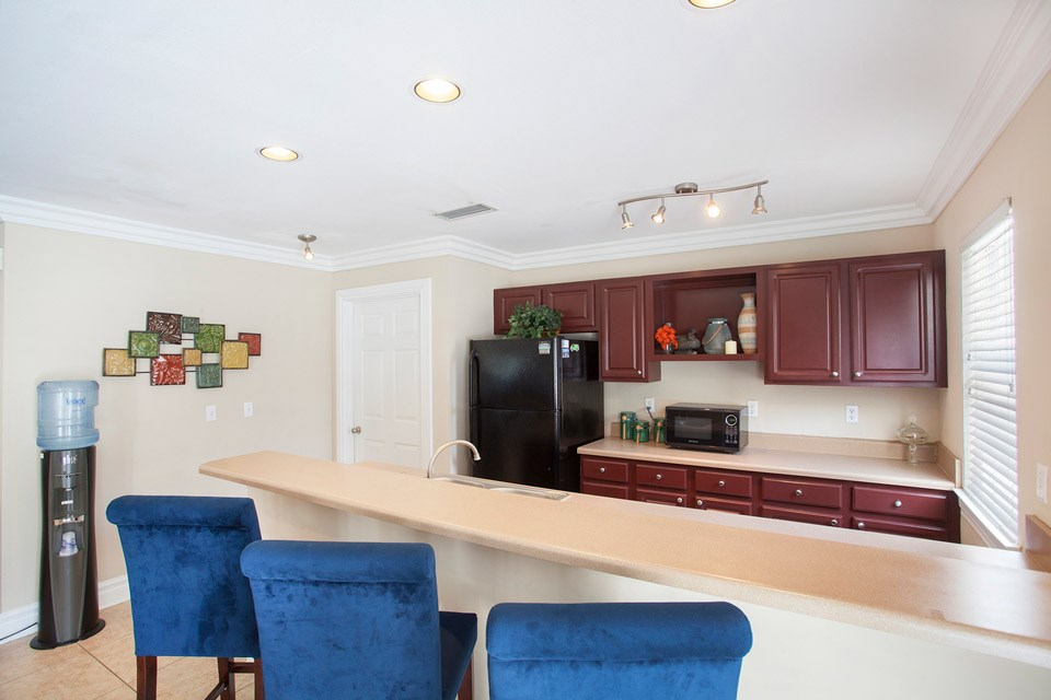 The kitchen area in the leasing office includes a bar, fridge, microwave and more at Crystal Lake Apartments in Pensacola, FL