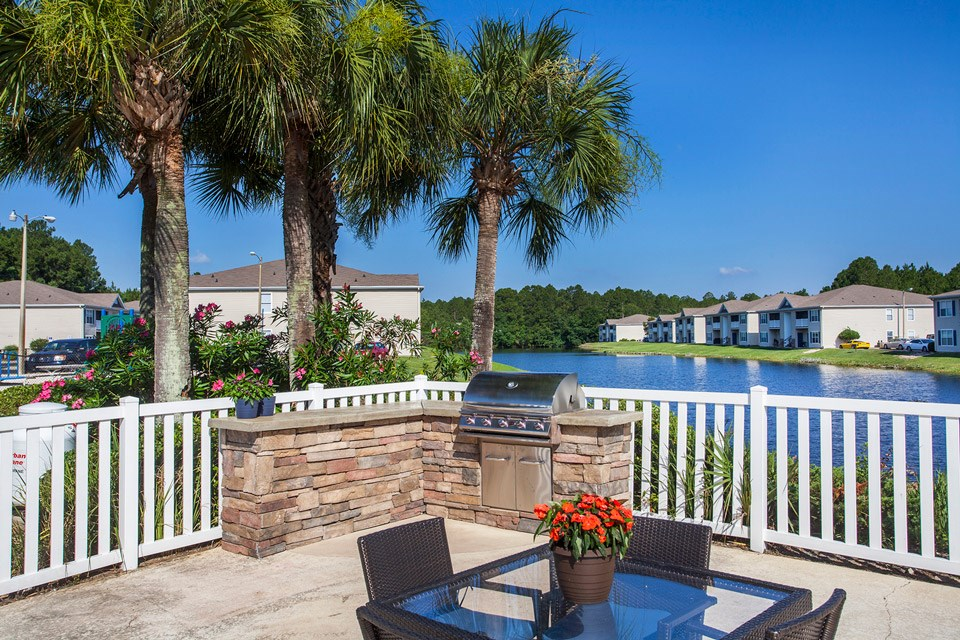 A large BBQ area with stone counter and glass table sit next to the beautiful lake at Crystal Lake Apartments in Pensacola, FL