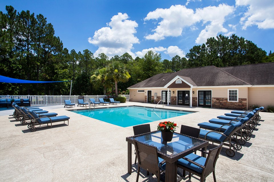 The leasing office and modern swimming pool surrounded by various tropical trees at Crystal Lake Apartments in Pensacola, FL
