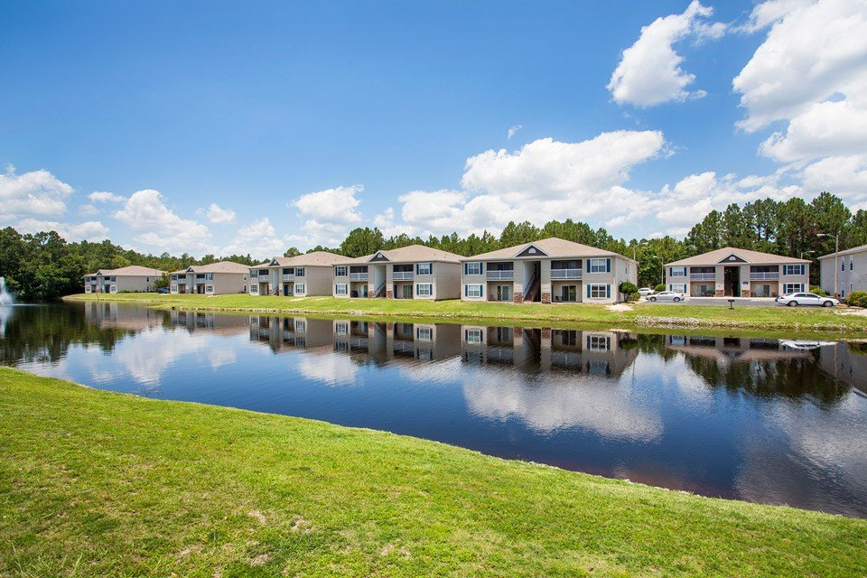 Multiple apartment buildings sit on the other side of the reflective stocked lake at Crystal Lake Apartments in Pensacola, FL