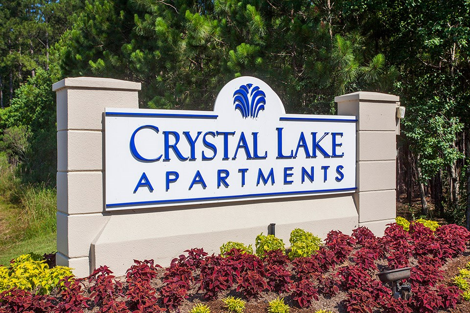 The entrance sign sits above numerous flourishing red and yellow plants at Crystal Lake Apartments in Pensacola, FL