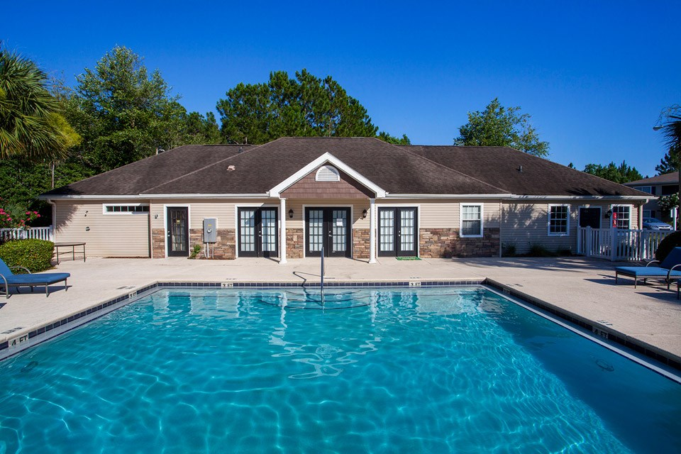 Crystal blue swimming pool water reflects the clear Florida sky above at Crystal Lake Apartments in Pensacola, FL