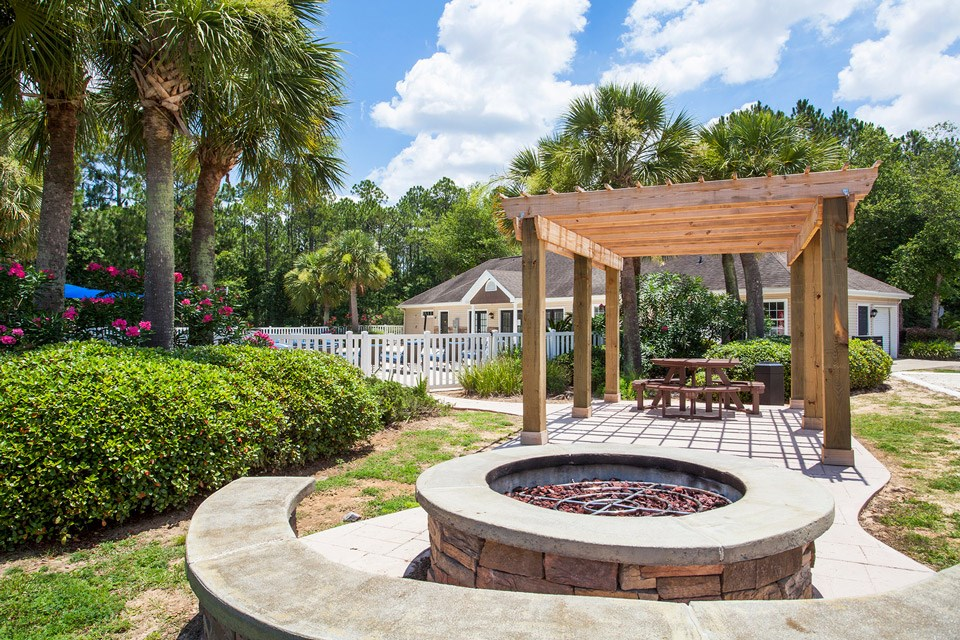 The fire pit area sits near the pool but just far enough for privacy at Crystal Lake Apartments in Pensacola, FL