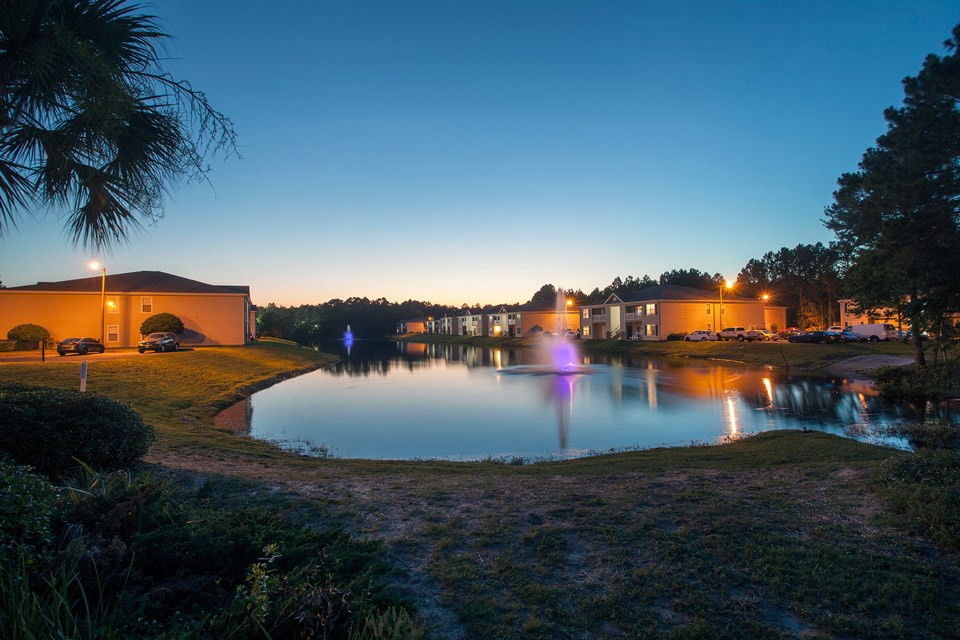 Two neon-lit fountains sit in the stocked lake as evening falls over Crystal Lake Apartments in Pensacola, FL
