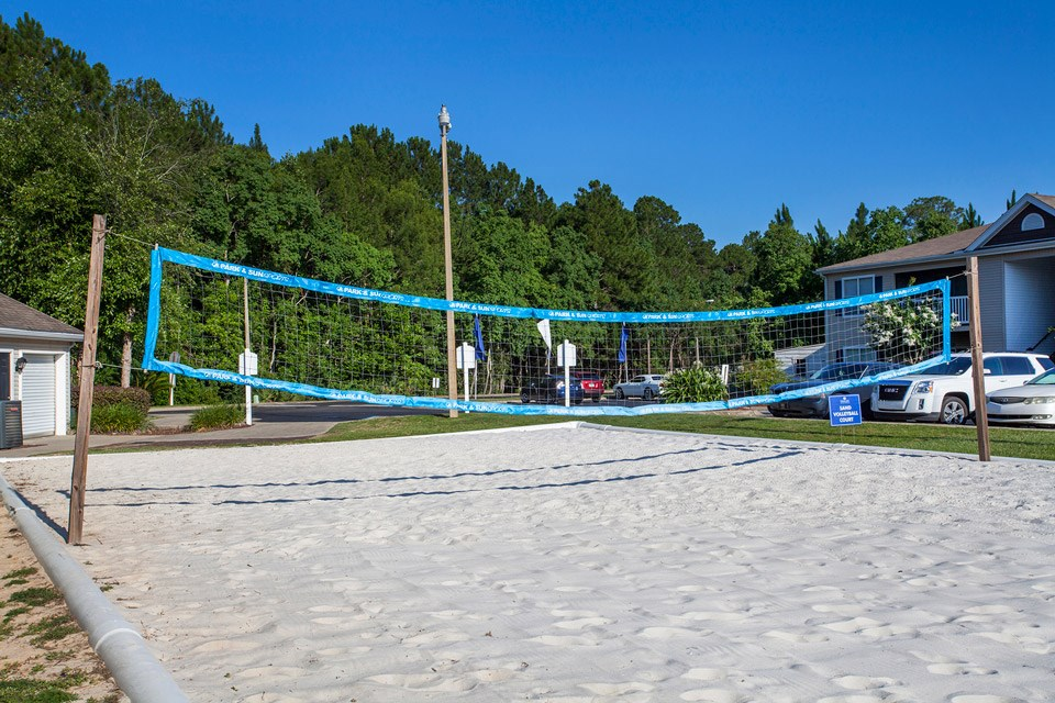 The net stands ready for action at the white sand volleyball court at Crystal Lake Apartments in Pensacola, FL