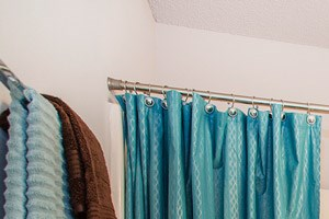 A turquoise shower curtain compliments the spotless white bathroom at Crystal Lake Apartments in Pensacola, FL