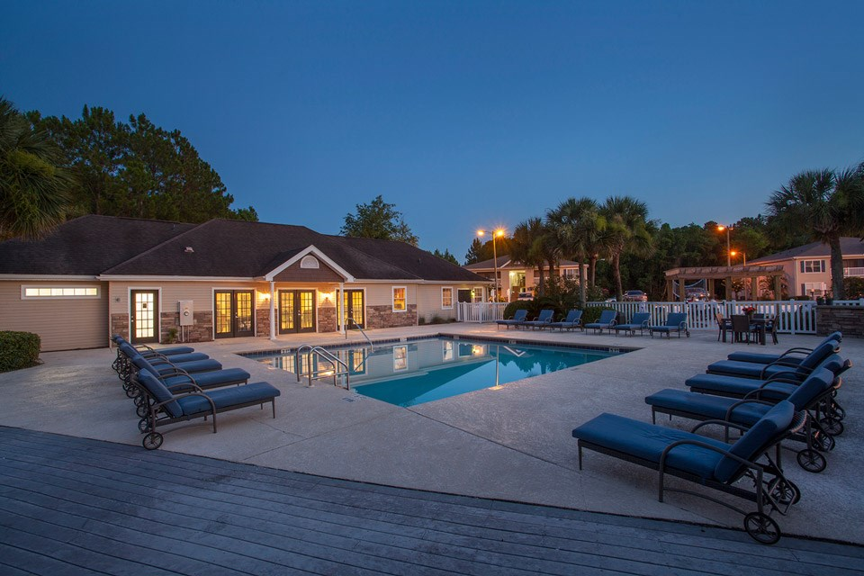 Evening falls over the swimming pool and poolside BBQ area at Crystal Lake Apartments in Pensacola, FL
