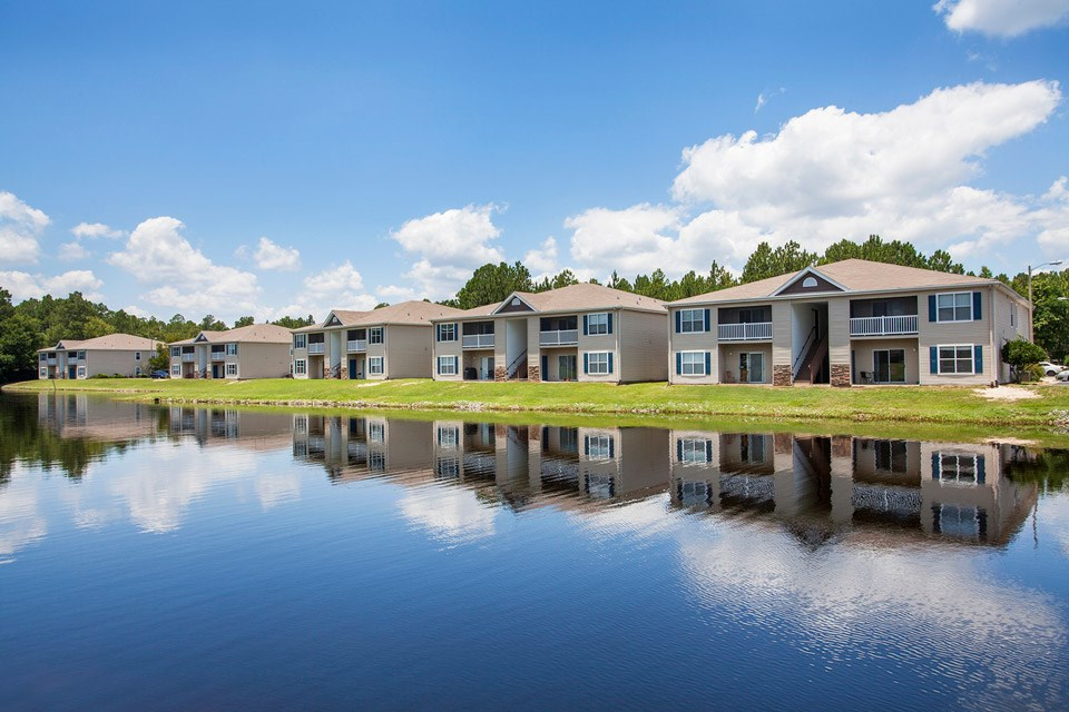 Clouds reflect off the surface of the stocked lake in front of multiple units at Crystal Lake Apartments in Pensacola, FL
