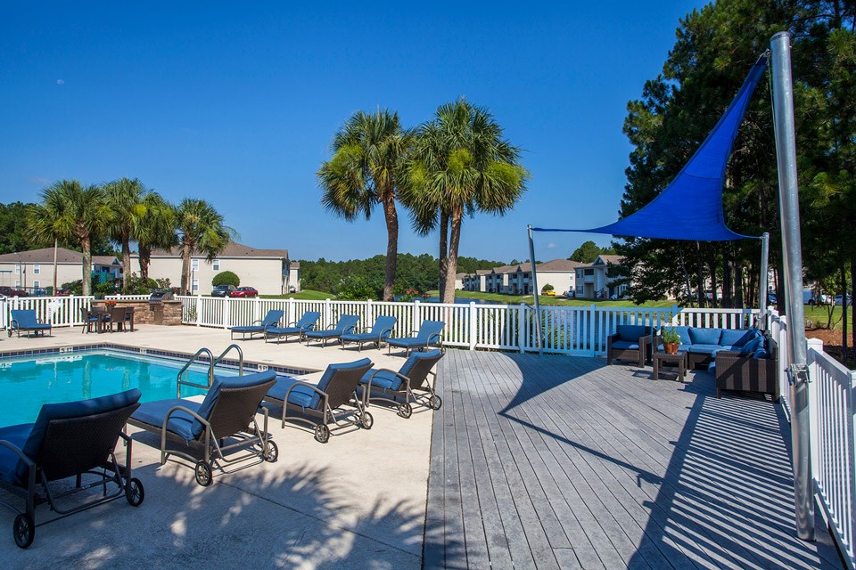 Palm trees stand over the modern pool and surrounding poolside lounge seating at Crystal Lake Apartments in Pensacola, FL